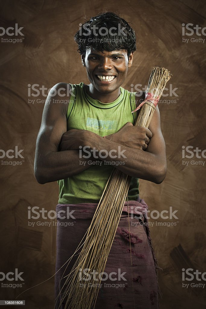 Happy, young, poor sweeper holding a broom stock photo