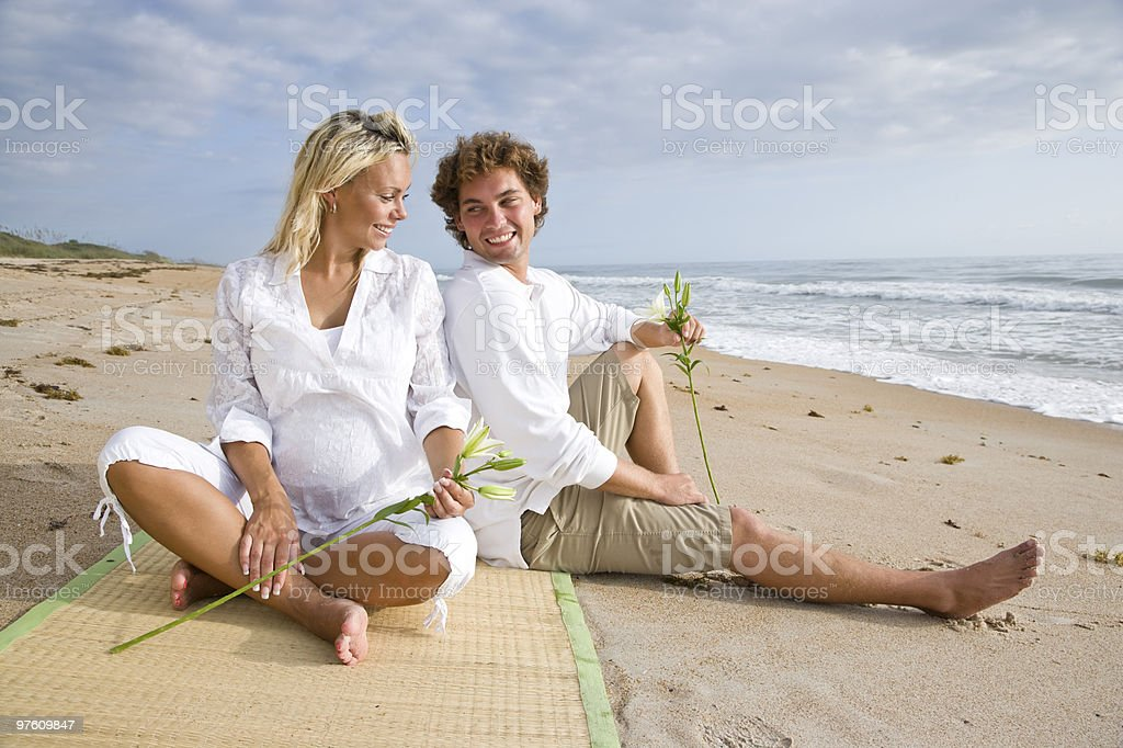 Happy young pregnant couple relaxing on beach royaltyfri bildbanksbilder