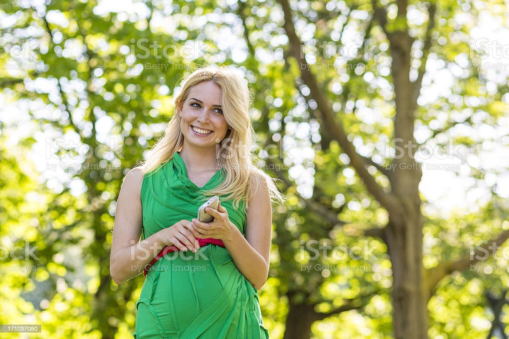 Happy young pregnant woman in the park stock photo