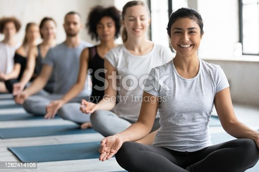 istock Happy young pretty indian ethnicity woman sitting in lotus pose. 1262414105