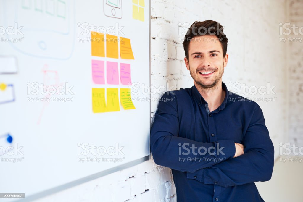 Happy young programmer, web designer standing at office stock photo