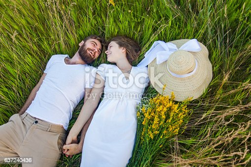 480122543 istock photo Happy young relaxed couple in love laying down on grass. 637240436