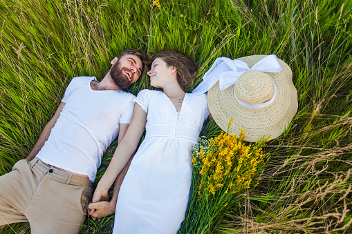 istock Happy young relaxed couple in love laying down on grass. 637240436