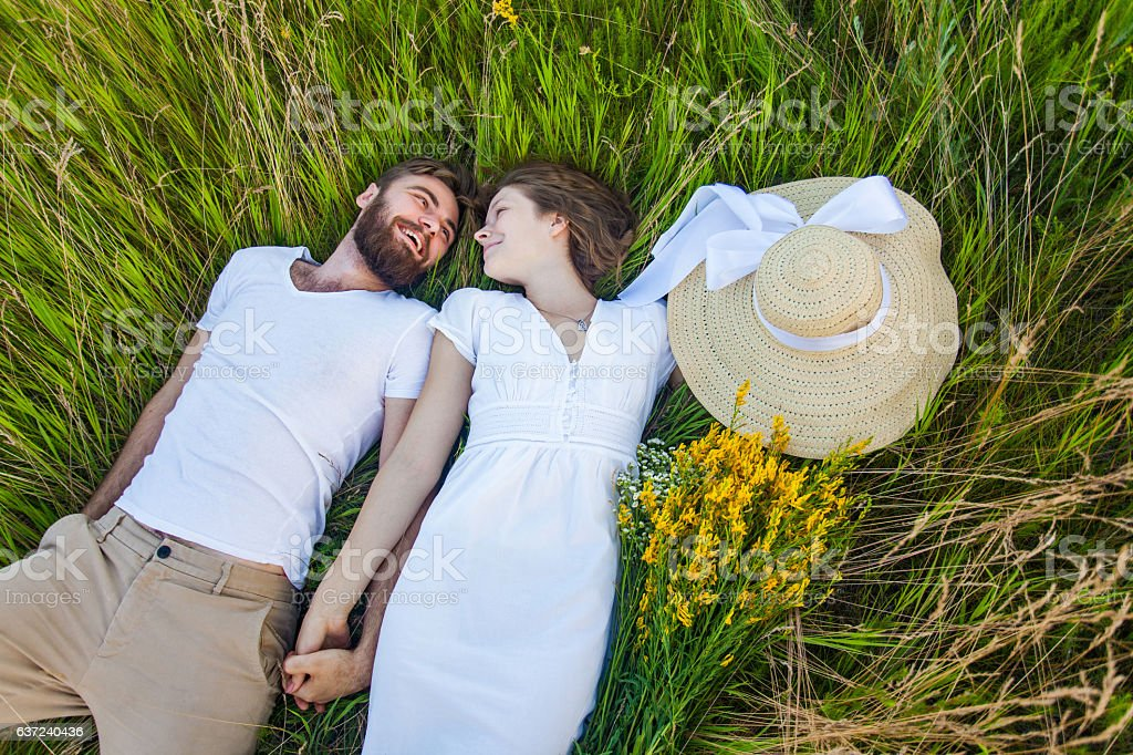 Happy young relaxed couple in love laying down on grass. – Foto