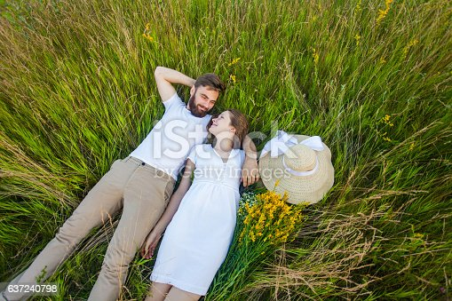 480122543 istock photo Happy young relaxed couple in love laying down on grass. 637240798