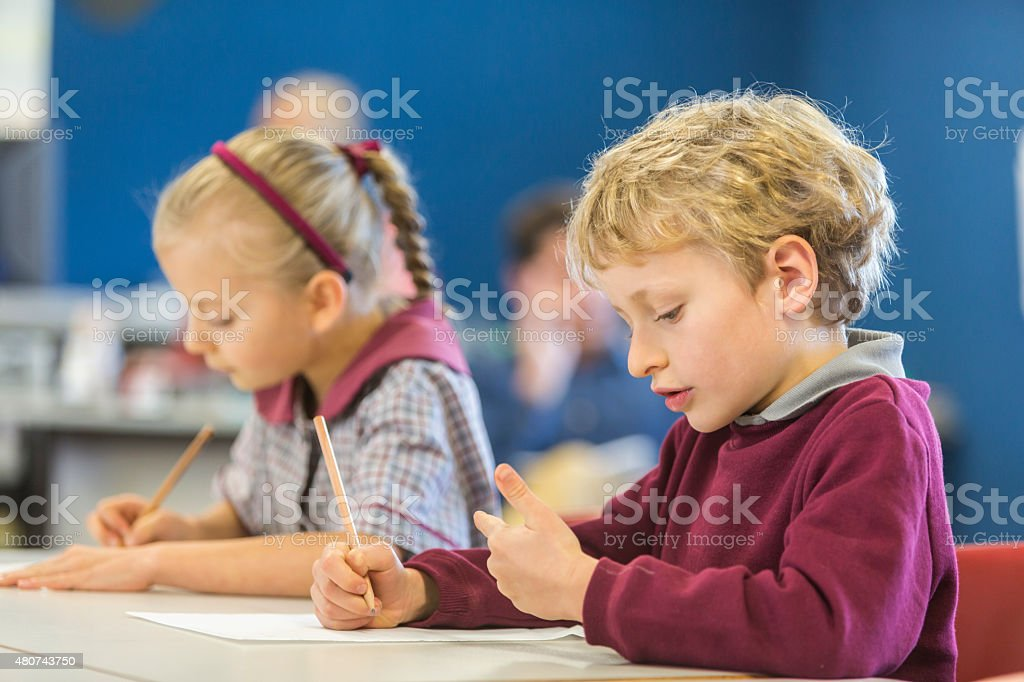 Happy Young School Boy Counting on His Fingers stock photo