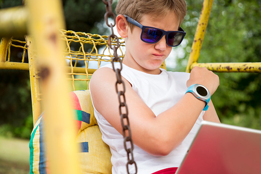 Happy young school boy reading playing video game on tablet in the park