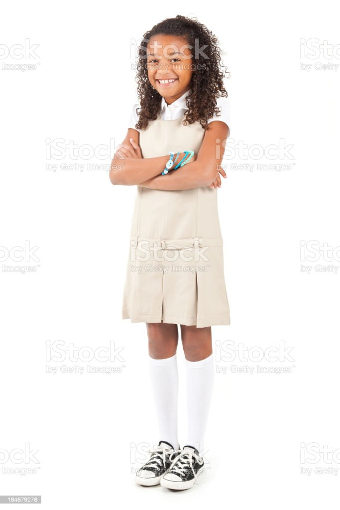 Happy young school girl in uniform with arms crossed royalty-free stock photo