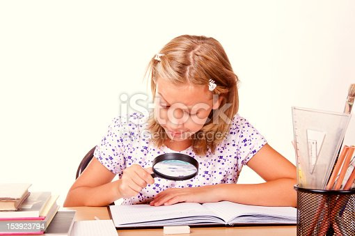 happy young school girl sit with a magnifying glass in hand and write homework