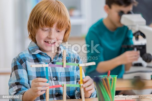 648947070 istock photo Happy young schoolboy creates something out of popsicle sticks 649355630
