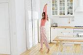 幸せな若い明るい白の日当たりの良いキッチンの自宅で踊っている少女の笑みを浮かべて、身に着けているピンクの格子縞パジャマ パンツ