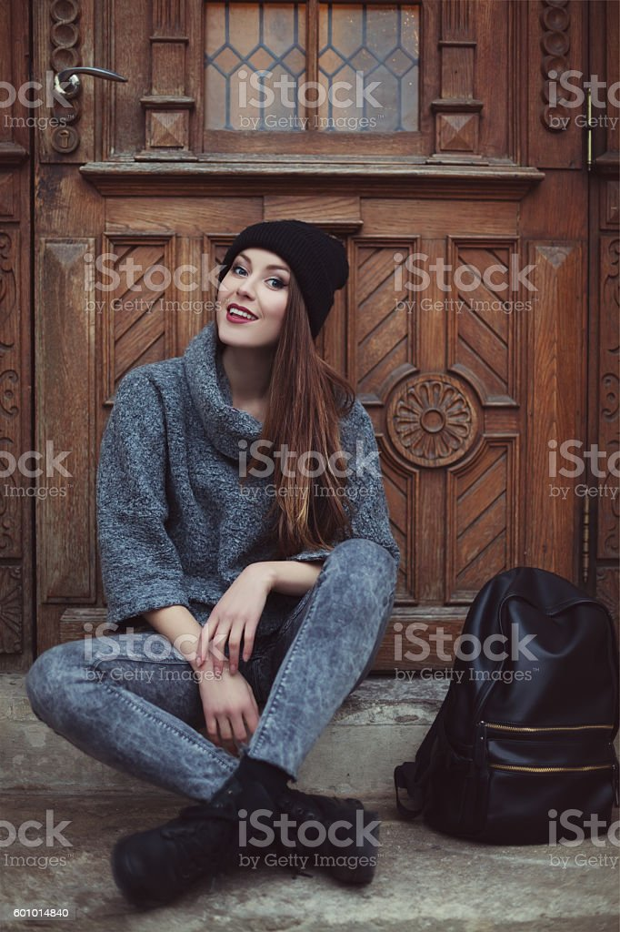 Happy young smiling hipster woman sitting near the door. Street – Foto