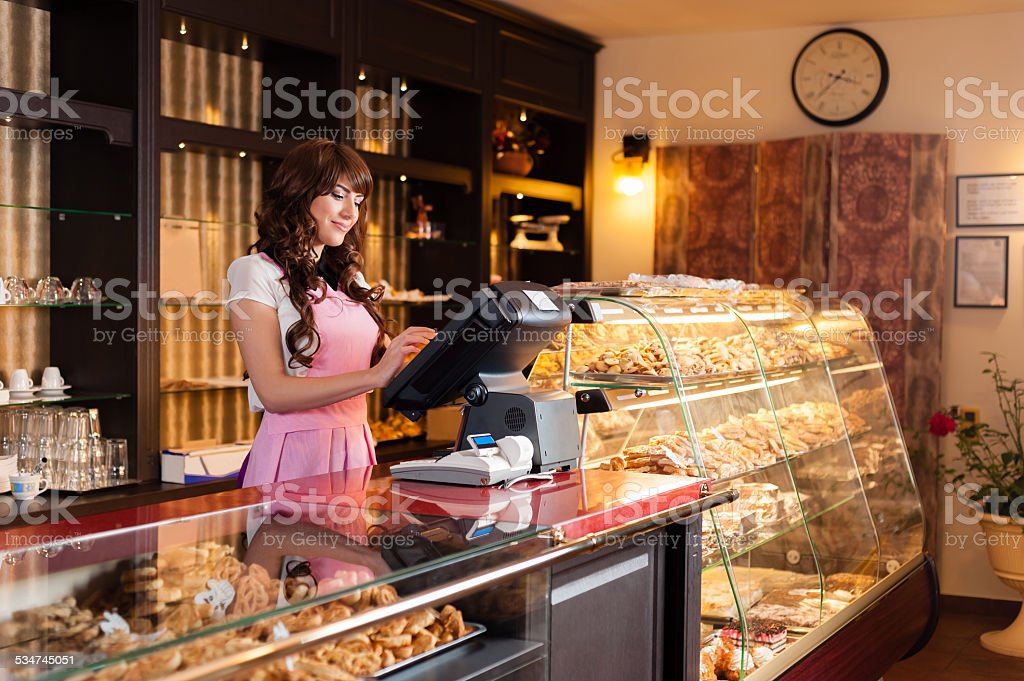 Happy young smiling seller in a cake shop stock photo