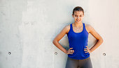 Happy sporty young woman in blue t-shirt with hands in waist ready for workout  against a white street wall. Copy space