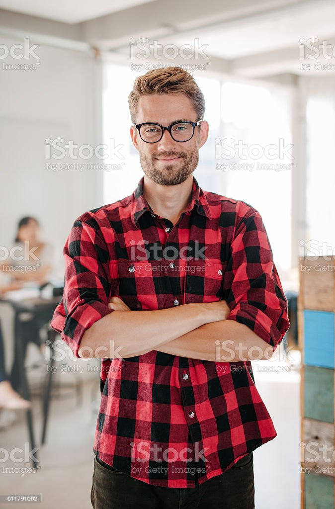 Happy young startup owner standing in office stock photo