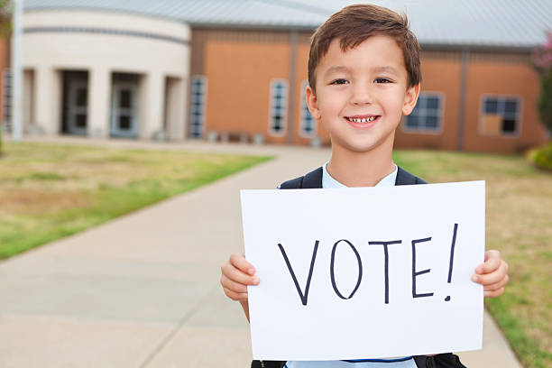 happy young student at school holding a vote sign - vote sign stock photos and pictures