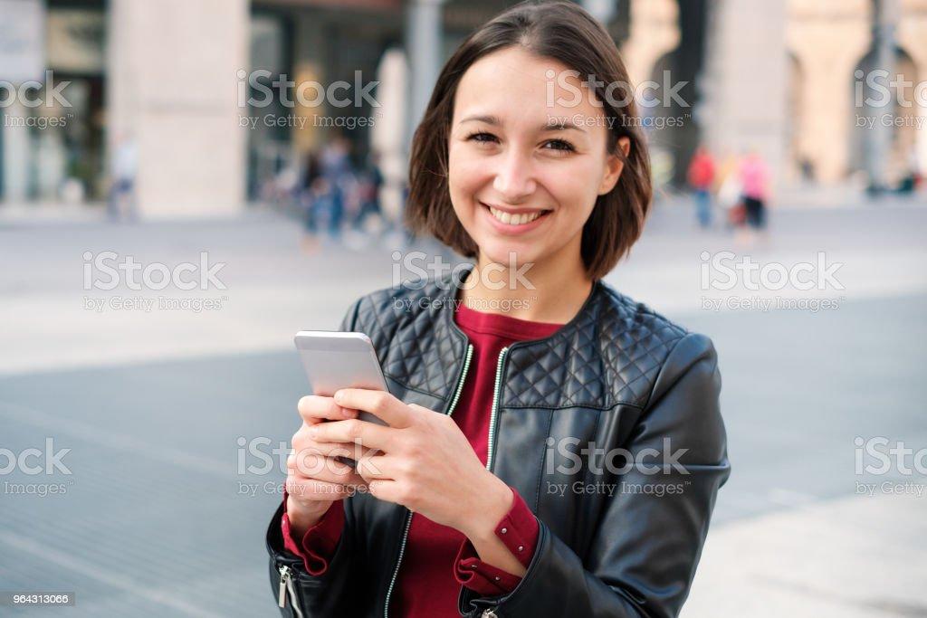 Feliz jovem estudante casual vestido usando o telefone - foto de acervo
