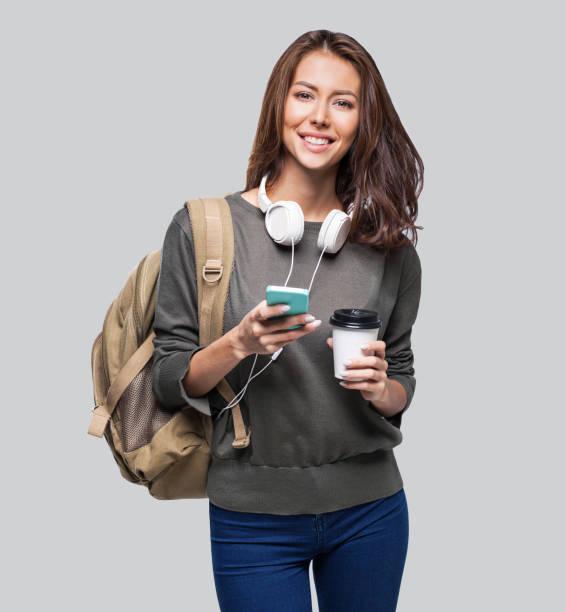 glückliche junge studentin mit smartphone - westeuropa stock-fotos und bilder
