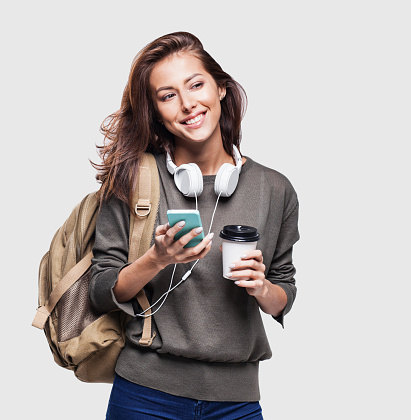 Happy young traveler girl holding smartphone and coffee