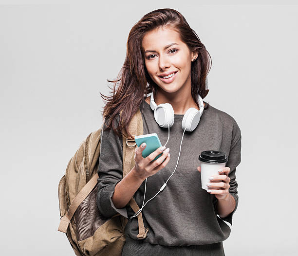 happy young student girl using smart phone - handytasche stock-fotos und bilder