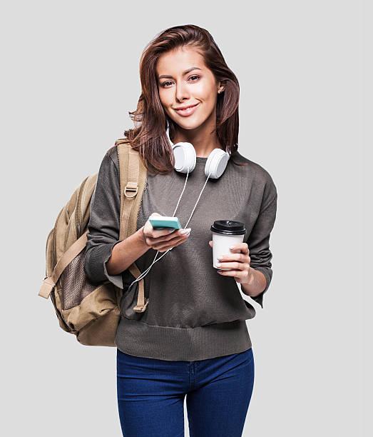 happy young student girl using smart phone - gesichtertassen stock-fotos und bilder