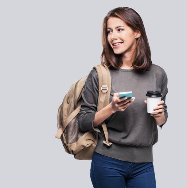 glückliche junge studentin mit smartphone - handytasche stock-fotos und bilder