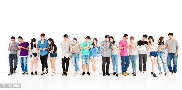 istock happy young student Group watching smart phone 644191686