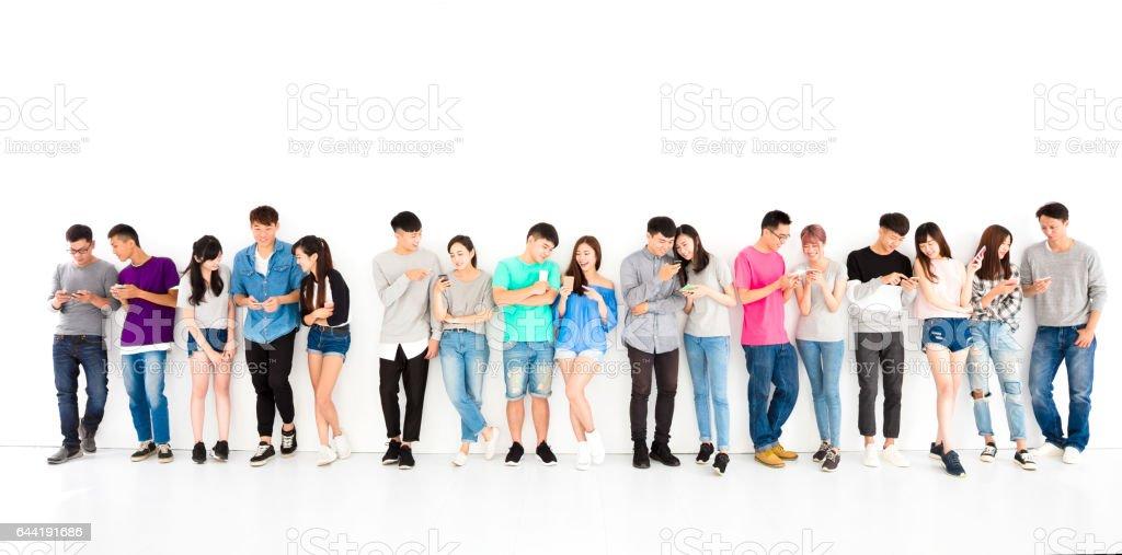 快樂的年輕學生組看智慧手機圖像檔