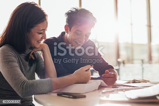 istock Happy young students reading a book together 622005332