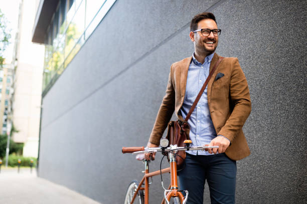 Happy young stylish businessman going to work by bike stock photo