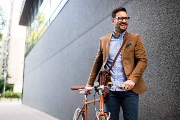 Glücklicher junger stylischer Geschäftsmann geht mit dem Fahrrad zur Arbeit – Foto