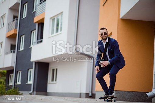 Happy young stylish businessman going to work by skateboard