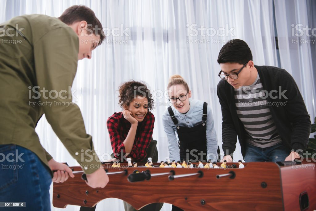 happy young teenagers playing in table soccer stock photo