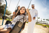 Happy young traditional family in Dubai, UAE at the park. The little girl playing on the swing with her dad and mom.