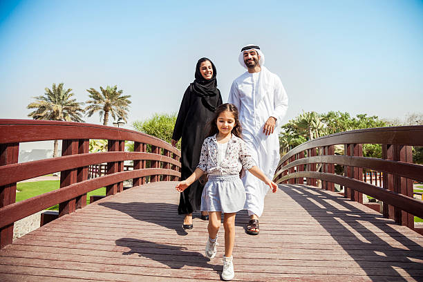 Happy young traditional family in Dubai, UAE Happy young traditional family in Dubai, UAE at the park. The little girl running in front of their parents in a beautiful sunny day. arabia stock pictures, royalty-free photos & images