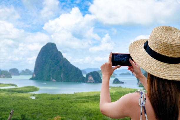 Happy Young Traveler Woman Raised Arm take a photo To Sky Enjoying A Beautiful Of Nature stock photo