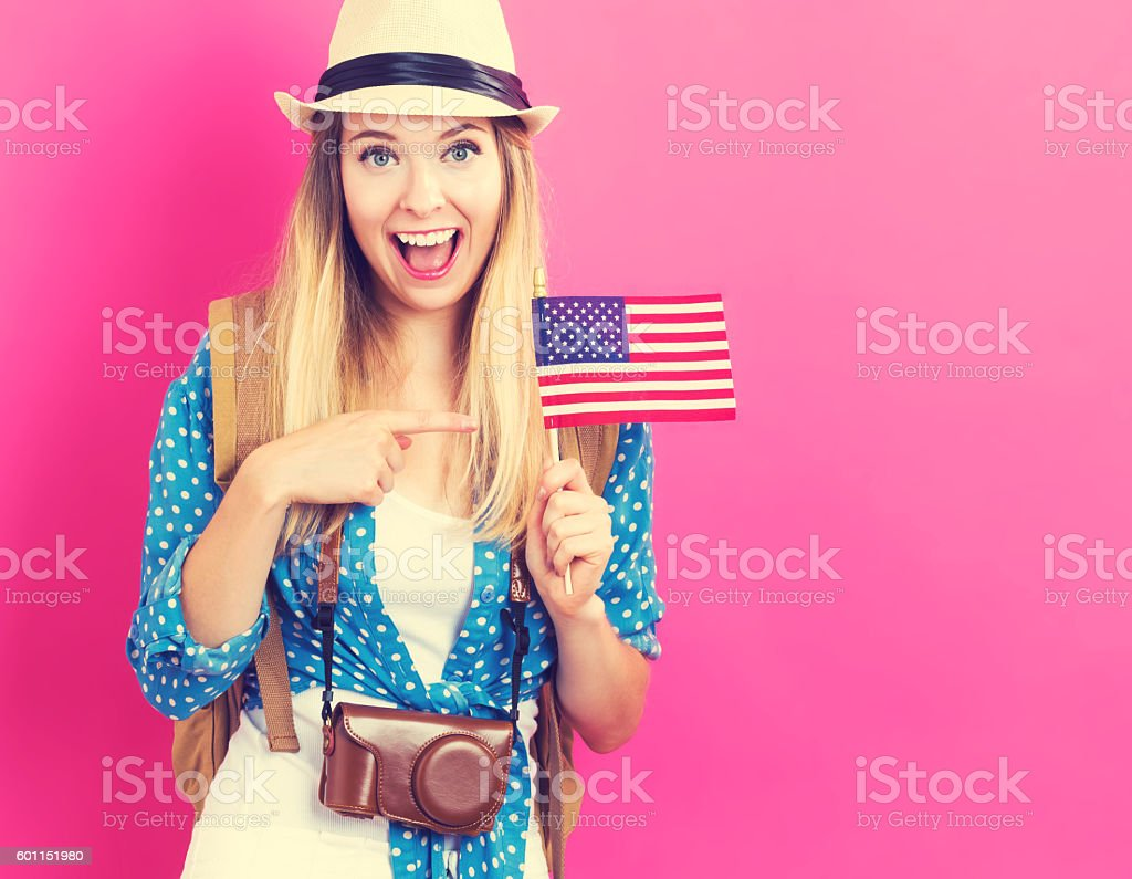 Happy young traveling woman holding American flag – Foto