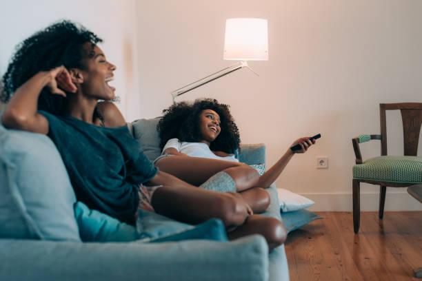 """glückliche junge schwarze zwei frauen liegen in der couch beobachten """"tvn - serien schauen stock-fotos und bilder"""