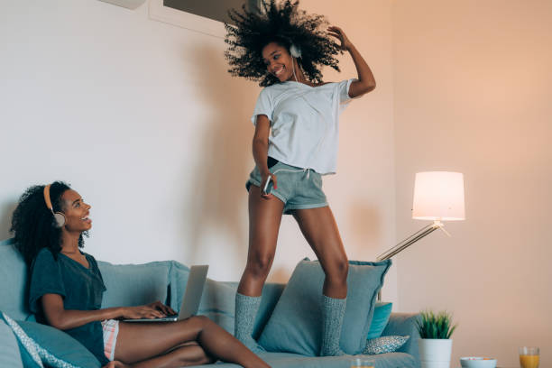Happy young two black women sitting and standing up in the couch on the computer and mobile phone with headphones dancing