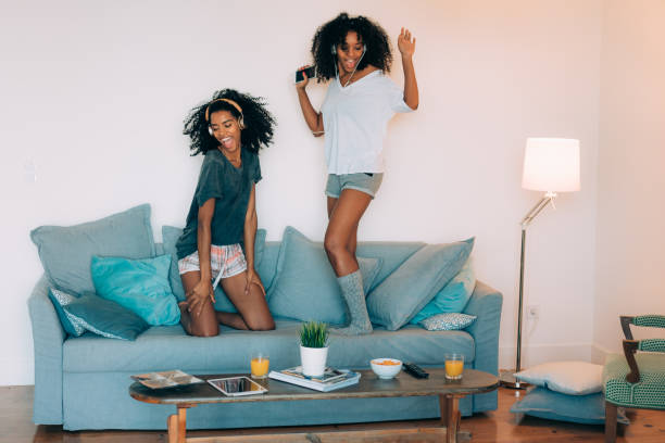 """happy young two black women sitting and standing up in the couch on the computer and mobile phone with headphones dancing """"n - dance music stock pictures, royalty-free photos & images"""