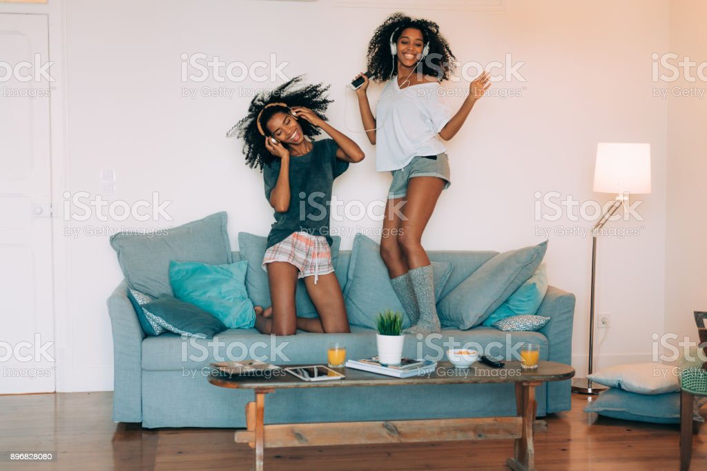 Happy young two black women sitting and standing up in the couch on the computer and mobile phone with headphones dancing 'n stock photo
