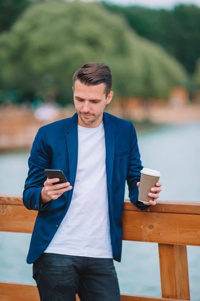 Glücklicher junger städtischer Mann arbeitet und trinkt Kaffee in der europäischen Stadt im Freien – Foto