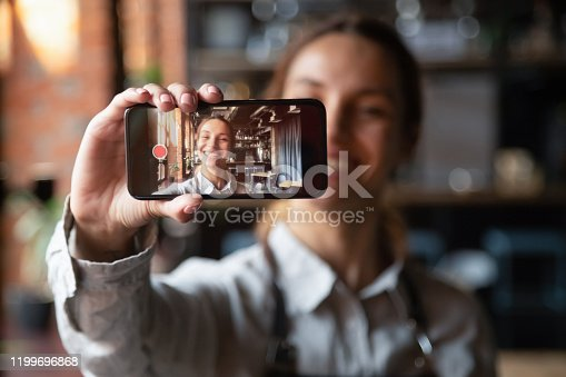Happy young waitress vlogger holding smartphone recording video blog on mobile display, smiling millennial cafe owner coffeehouse worker blogger girl wear apron shooting vlog looking at phone camera