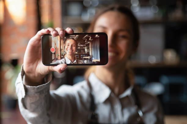 glückliche junge kellnerin vlogger halten smartphone aufnahme video-blog - fotohandy stock-fotos und bilder