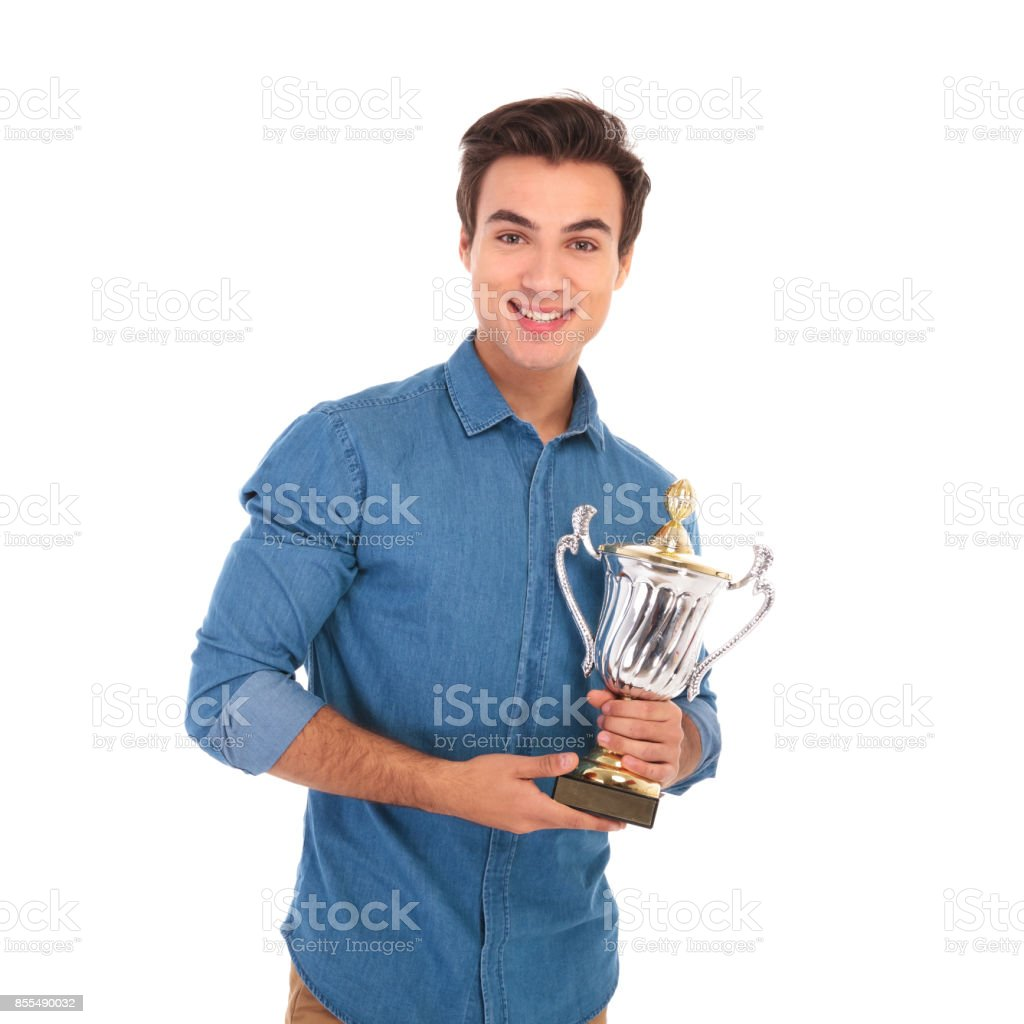 happy young winner holding his trophy prize and smiles stock photo