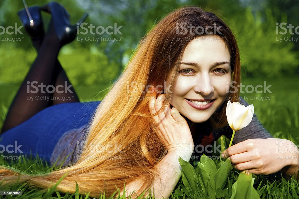 Happy young woman and flower in fresh grass royalty-free stock photo