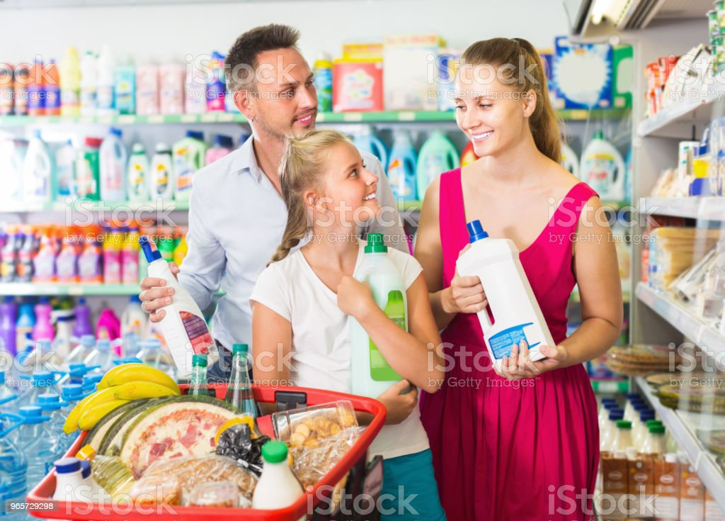 Happy young woman and man with child choosing detergent - Royalty-free 20-29 Years Stock Photo
