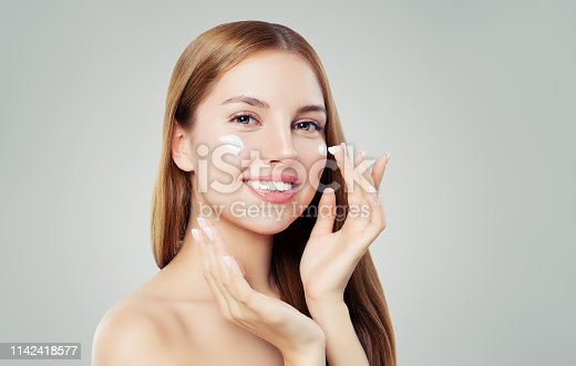 istock Happy young woman applying cream on her face. Skin care, beauty and facial treatment concept 1142418577