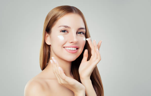 Happy young woman applying cream on her face. Skin care, beauty and facial treatment concept Happy young woman applying cream on her face. Skin care, beauty and facial treatment concept one young woman only stock pictures, royalty-free photos & images