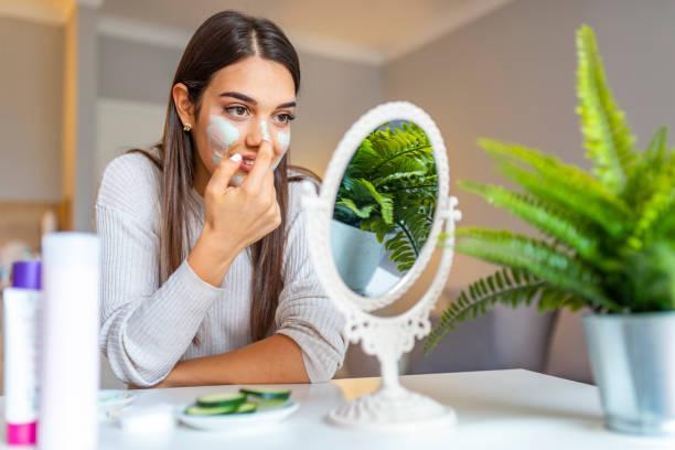 gelukkige jonge vrouw aanbrengen gezichtsmasker thuis en glimlachend. - mirror mask stockfoto's en -beelden